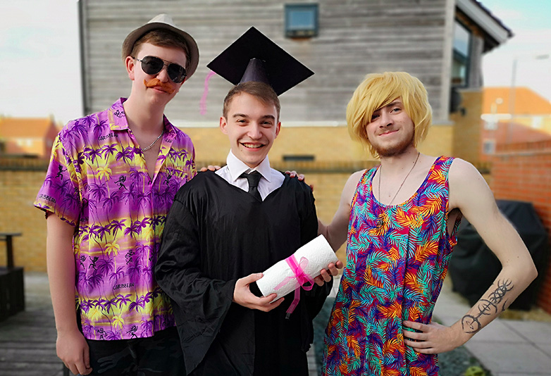 Guy and his mates posing at fake graduation