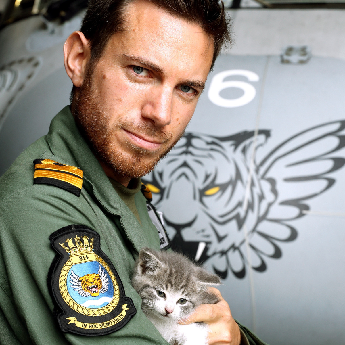 "Nick Grimmer with Tigger the kitten. See SWNS story SWKITTEN. Meet Tigger – the kitten which survived a 300-mile journey hiding INSIDE the bumper of a navy helicopter pilot's car. The cat endured a day's journey from Birmingham Airport to the Royal Naval Air Station Culdrose near Helston in Cornwall clinging to the rear bumper of Lieutenant Nick Grimmer's BMW. It was only the day after the epic journey that 32-year-old Nick heard ""very quiet meowing"" coming from his car – and began to investigate. ""I'd landed at Birmingham after a holiday and travelled via Bristol and Bath before arriving in Cornwall quite late,"" said Nick, who flies submarine–hunting Merlin helicopters for a living with 814 Naval Air Squadron – known as the Flying Tigers. ""I looked in the boot, under the bonnet and climbed all over and under it and still couldn't find what was making the noise. ""I called up some of our air engineers who came and helped me to start dismantling my pride and joy. On taking off the rear bumper we were greeted by a tiny tiger-striped kitten. ""He must have had a long journey but remarkably is unharmed. I am never late for work and was left with no option but to take my new friend in with me. The place he has felt most comfortable is in my flying helmet, which is the only place he is able to sleep."""