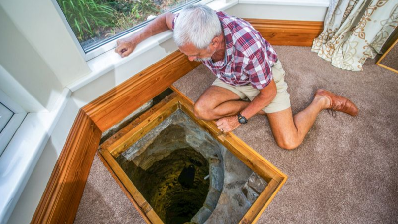 Man digging under sofa