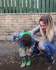 Toddler splashes in puddle for the first time.