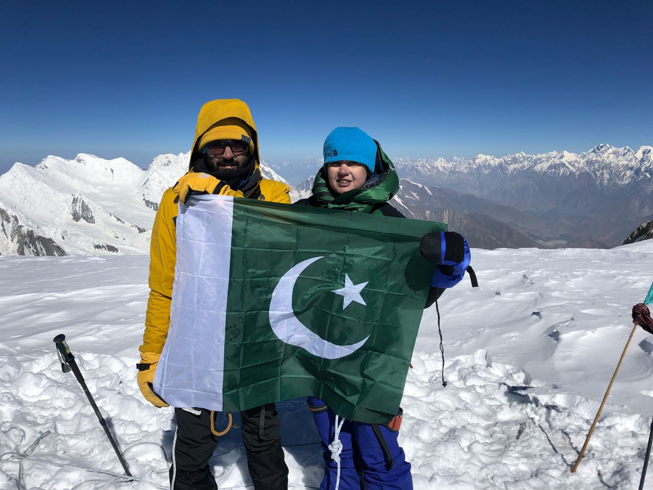 Guys holding Pakistani flag on mountain