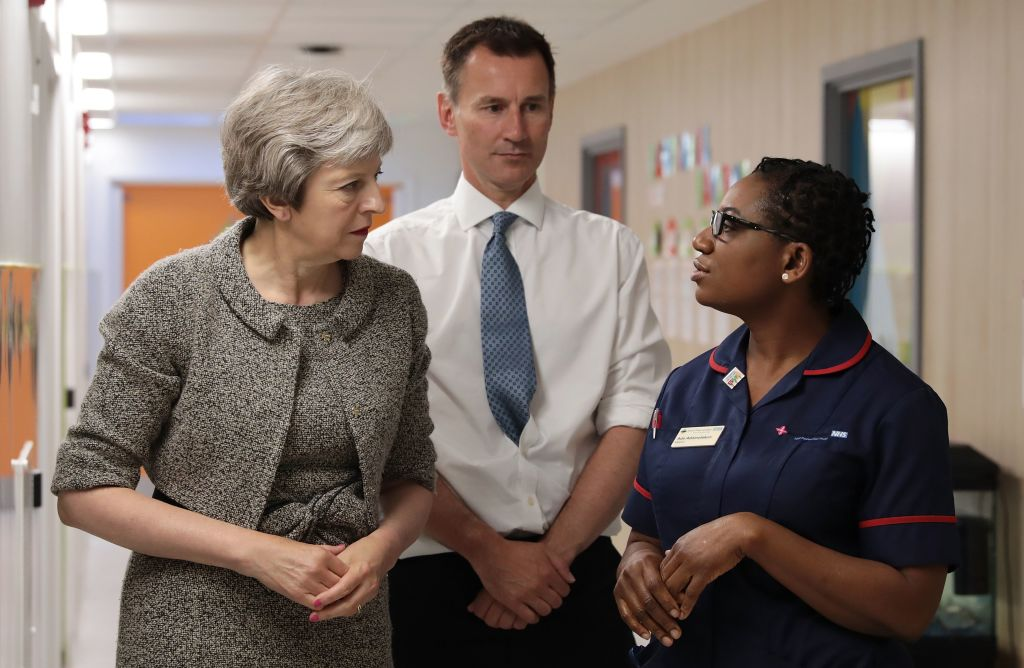 Theresa May (L) and Britain's Health and Social Care Secretary Jeremy Hunt (C)