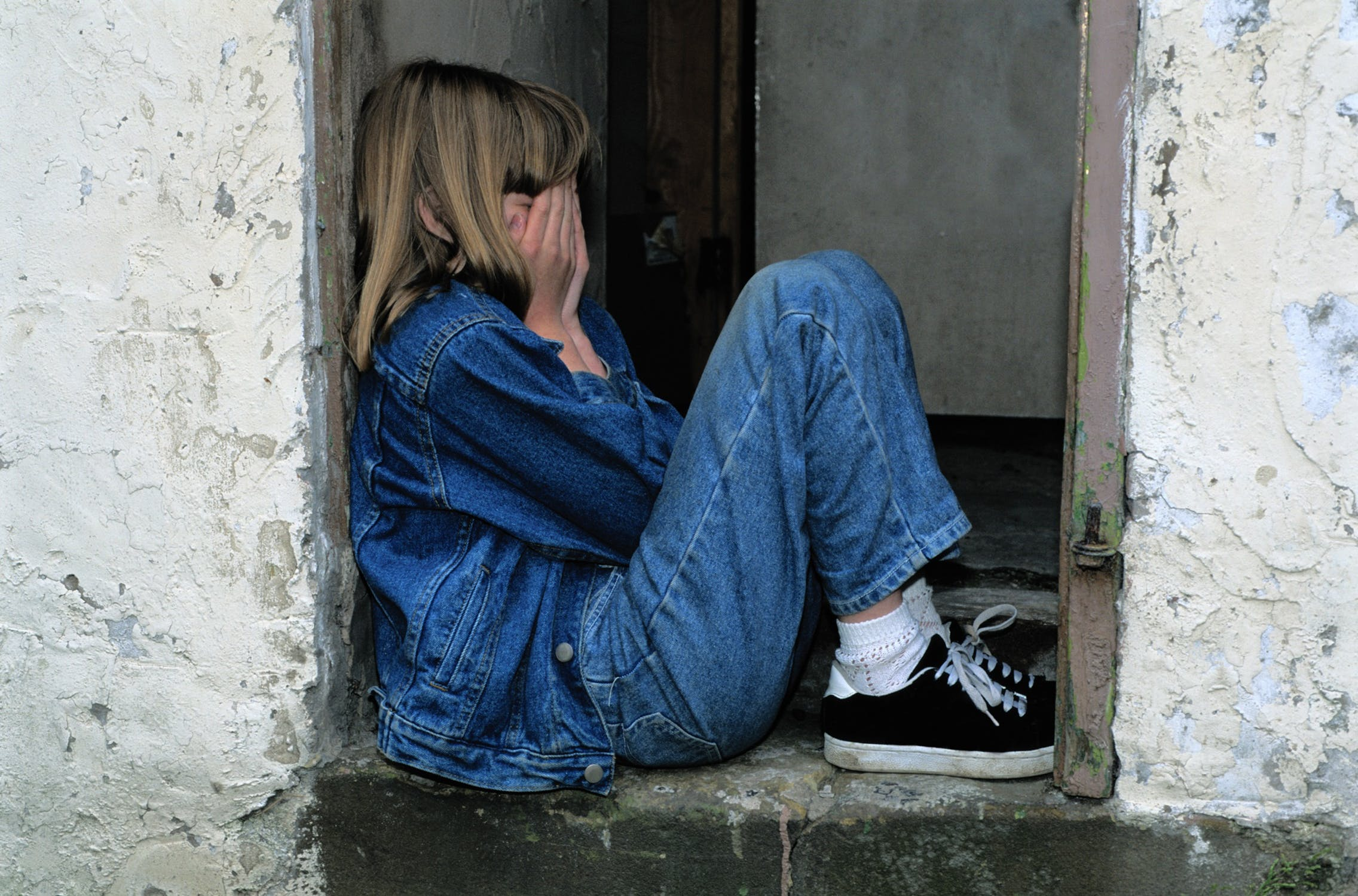 Young girl wwearing double denim with head in hands