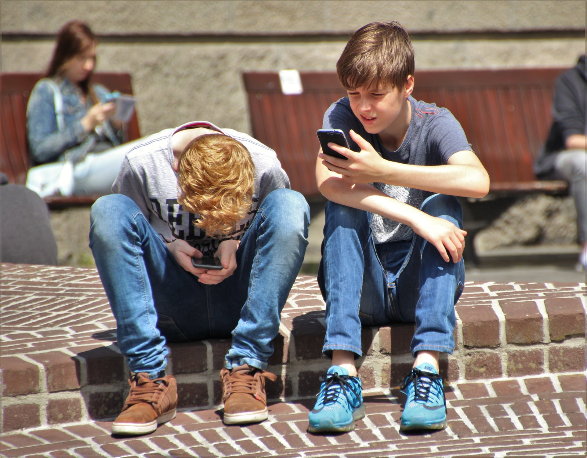 Two children sitting on their smartphones
