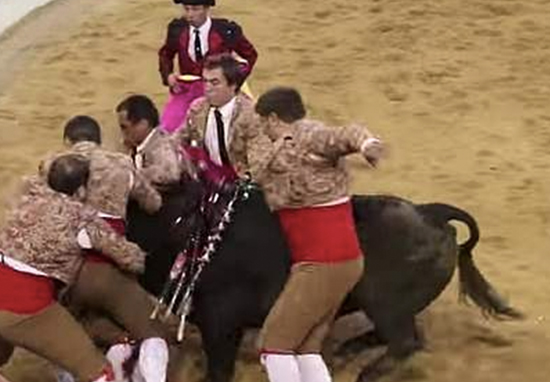 Bullfighters charged by bull.