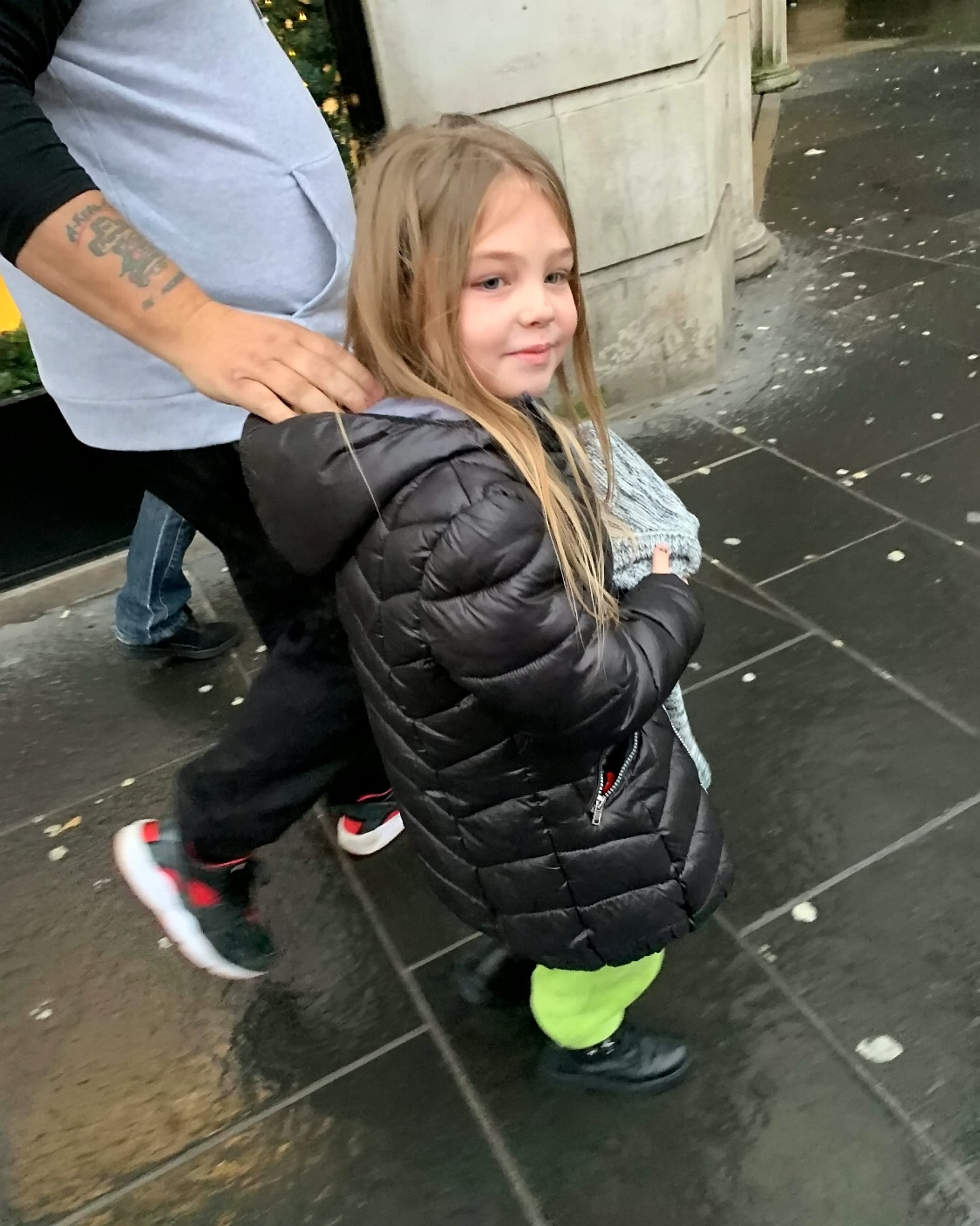 Young girl hands out food to homeless people