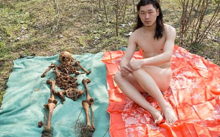 Artist takes picture of himself with his father's bones.