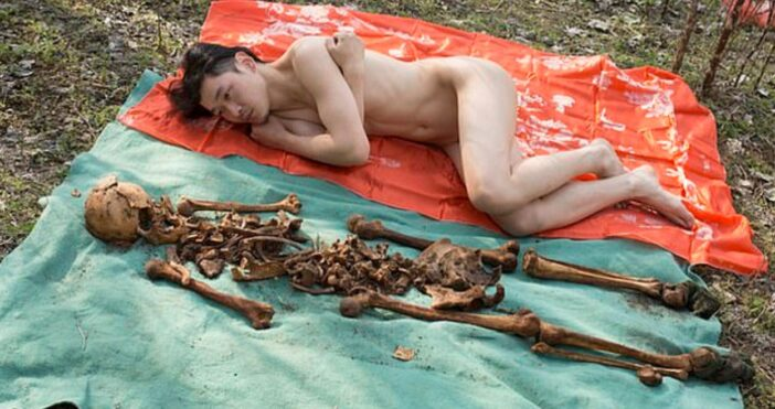 Artist shares pictures of himself lying beside his father's skeleton.