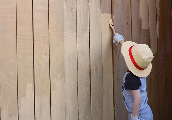 Child painting fence