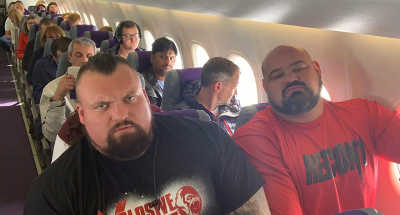 Eddie Hall and Brian Shaw sit next to each other on a plane.