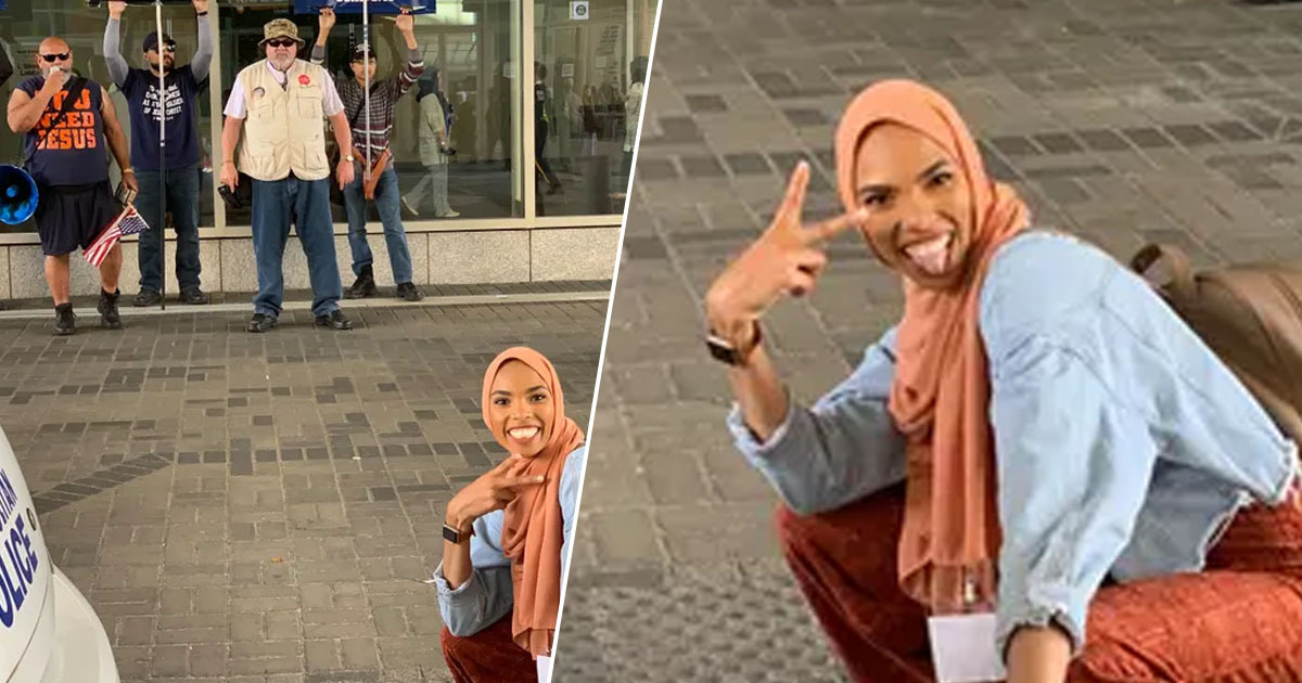 smiling woman taking photo in front of ant-islam protestors