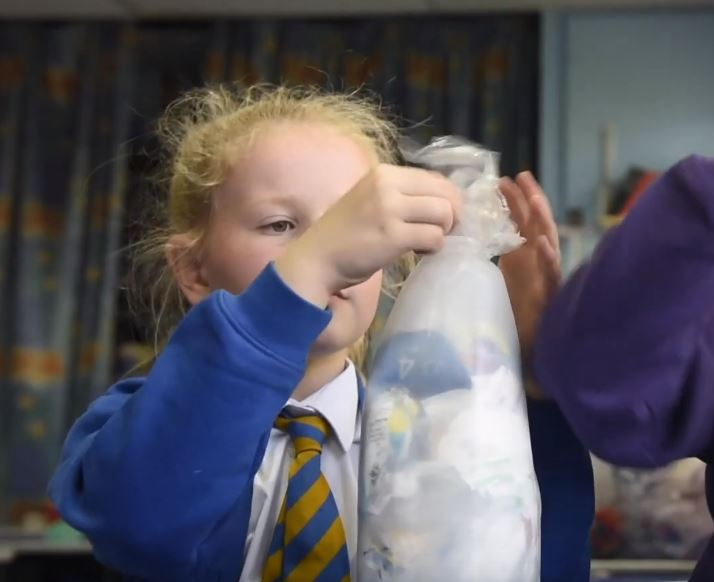 Children fill plastic bottles to create eco bricks and build classroom