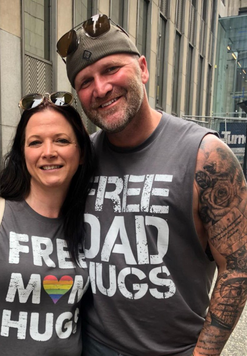 couple with 'free dad hugs' and 'free mom hugs' t shirts