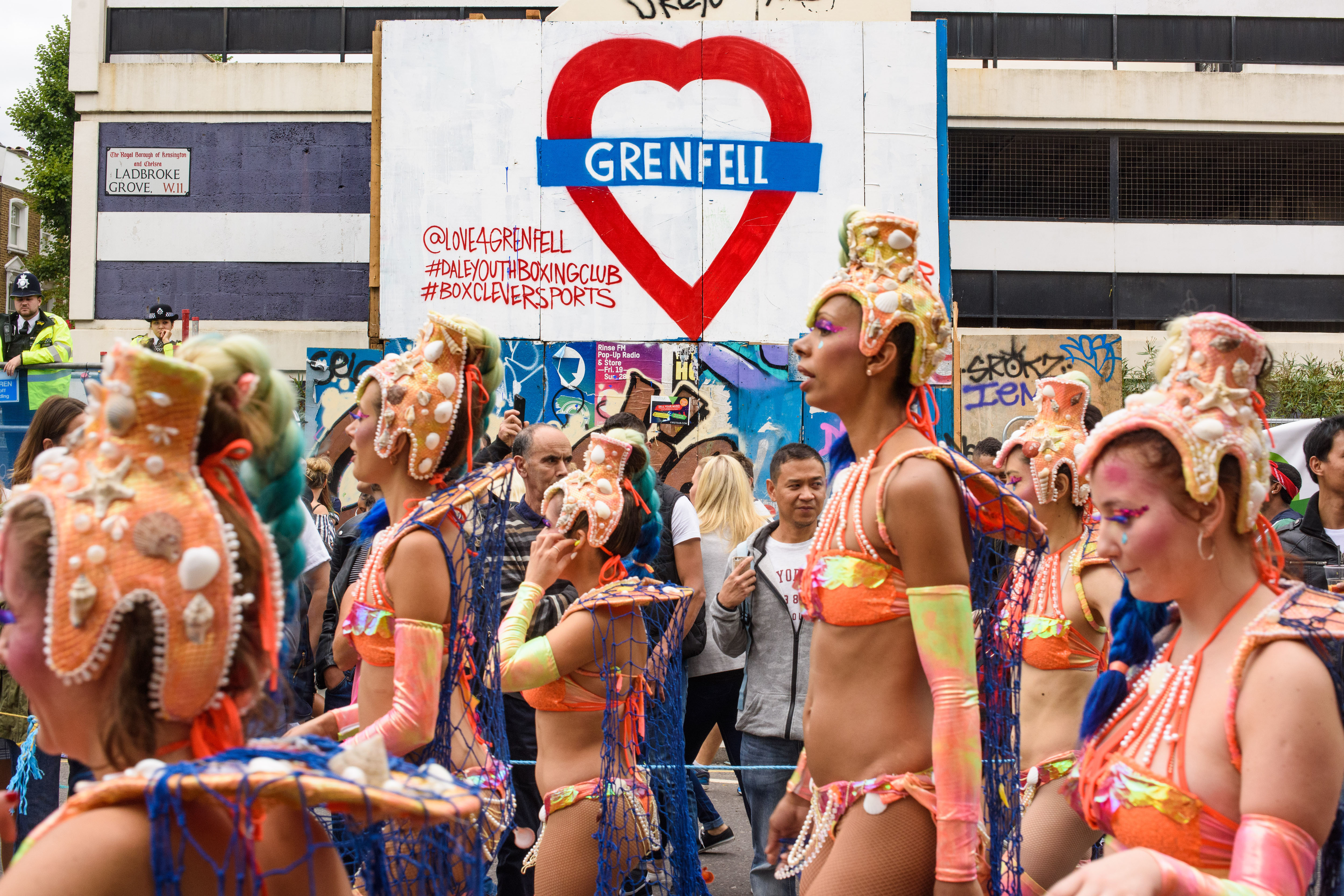 notting hill carnival parade past grenfell sign