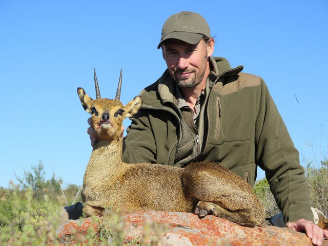 Trophy hunters pose with animal