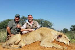 trophy hunters posing with lion