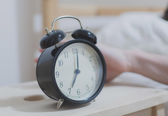 Person snoozing alarm clock