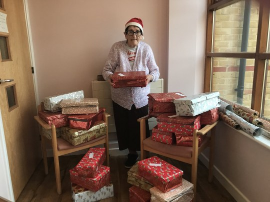 Grandmother stands with shoeboxes she's made for people in need