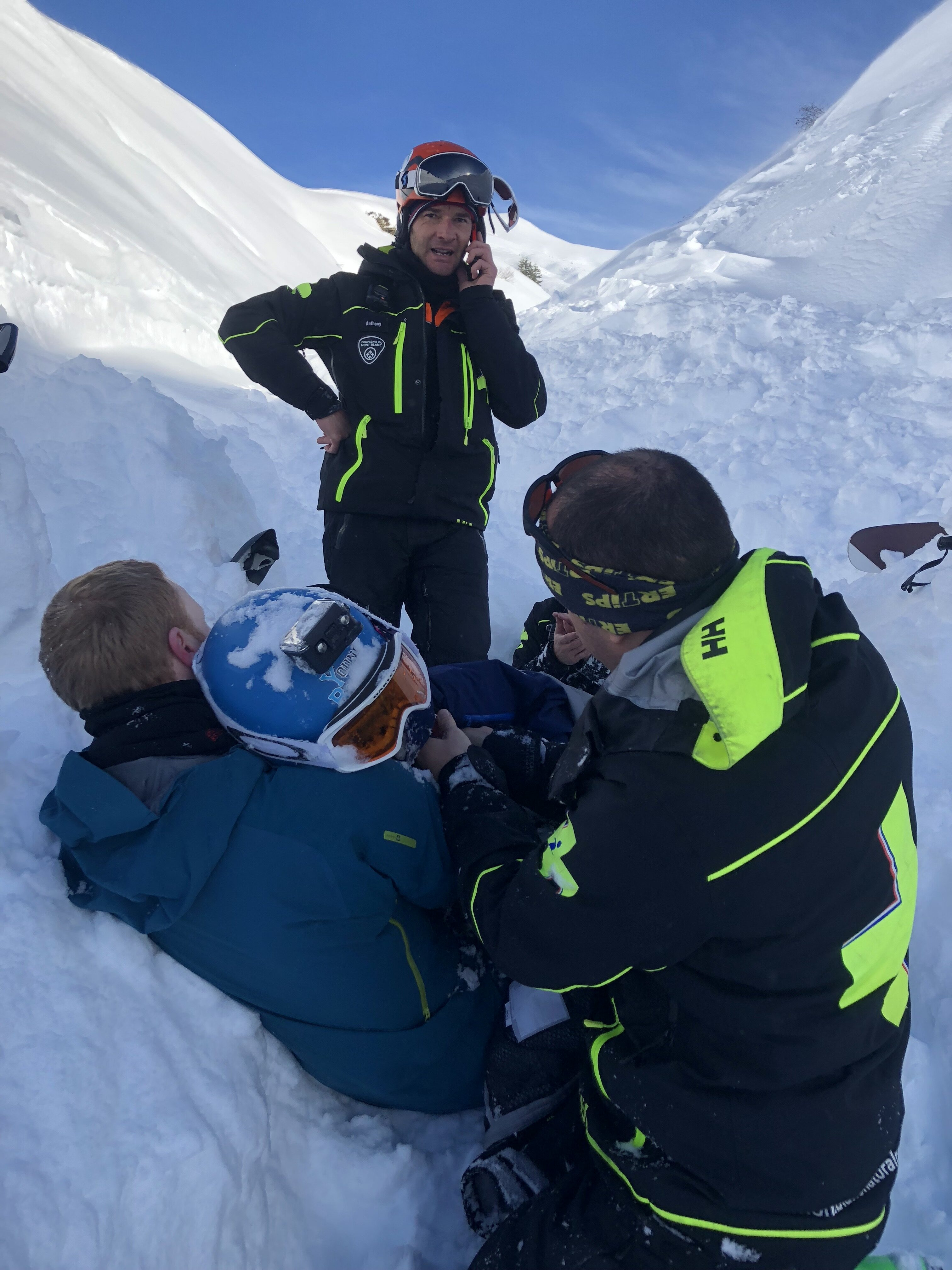 11-year-old boy with rescuers after being buried by snow