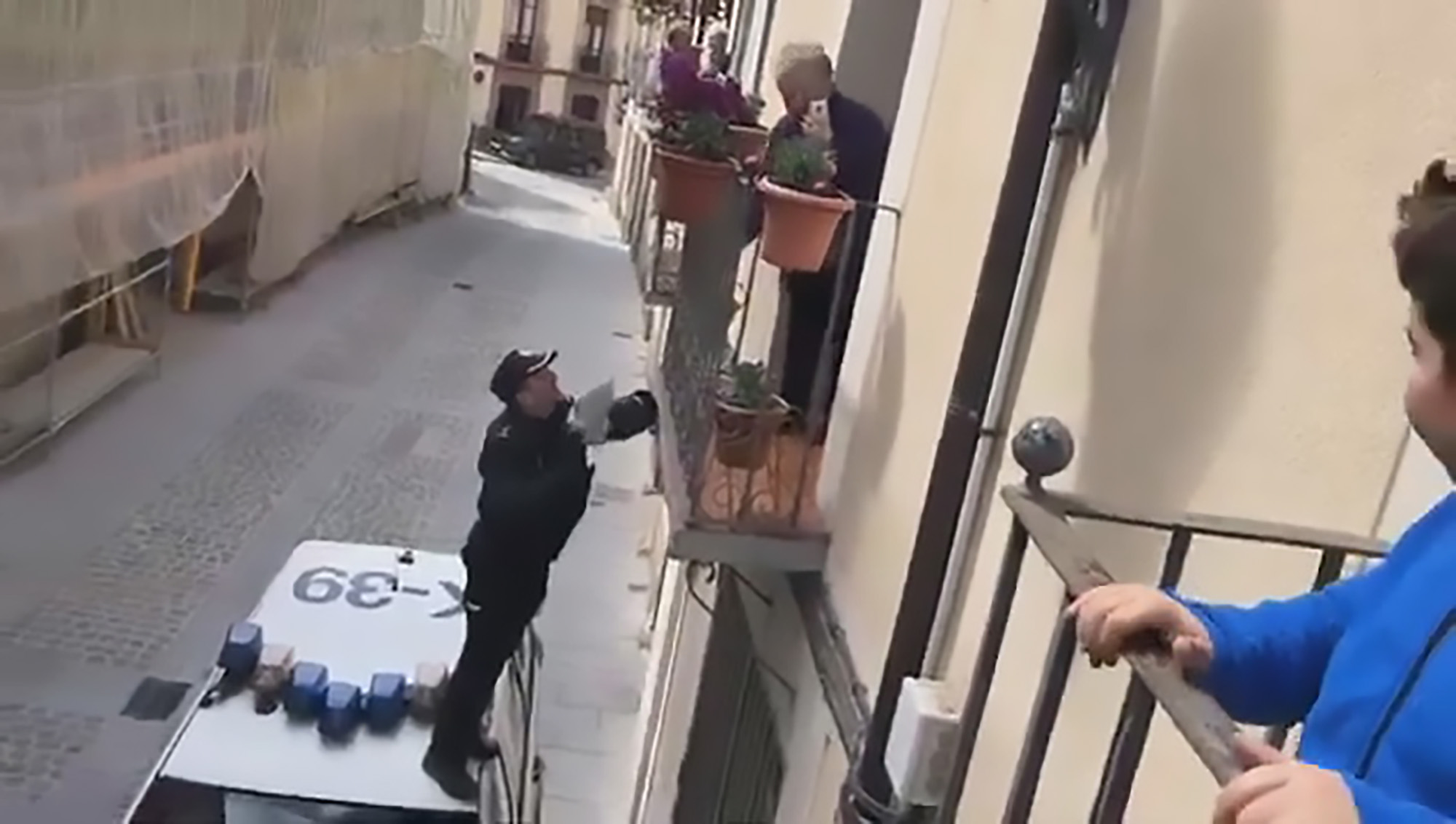 Pensioner comes on to balcony to see officer offering sweets