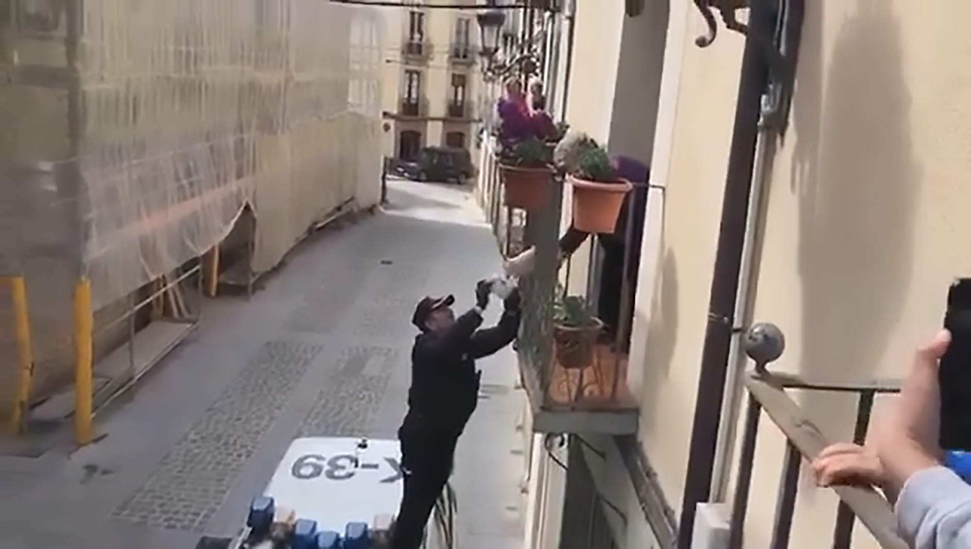 Police officer handing sweets to pensioner
