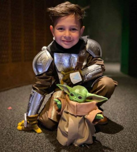 4-year-old in Mandalorian cosplay with Baby Yoda