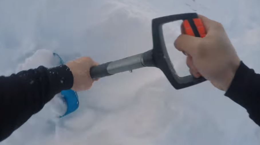Father digging son out of hole under snow