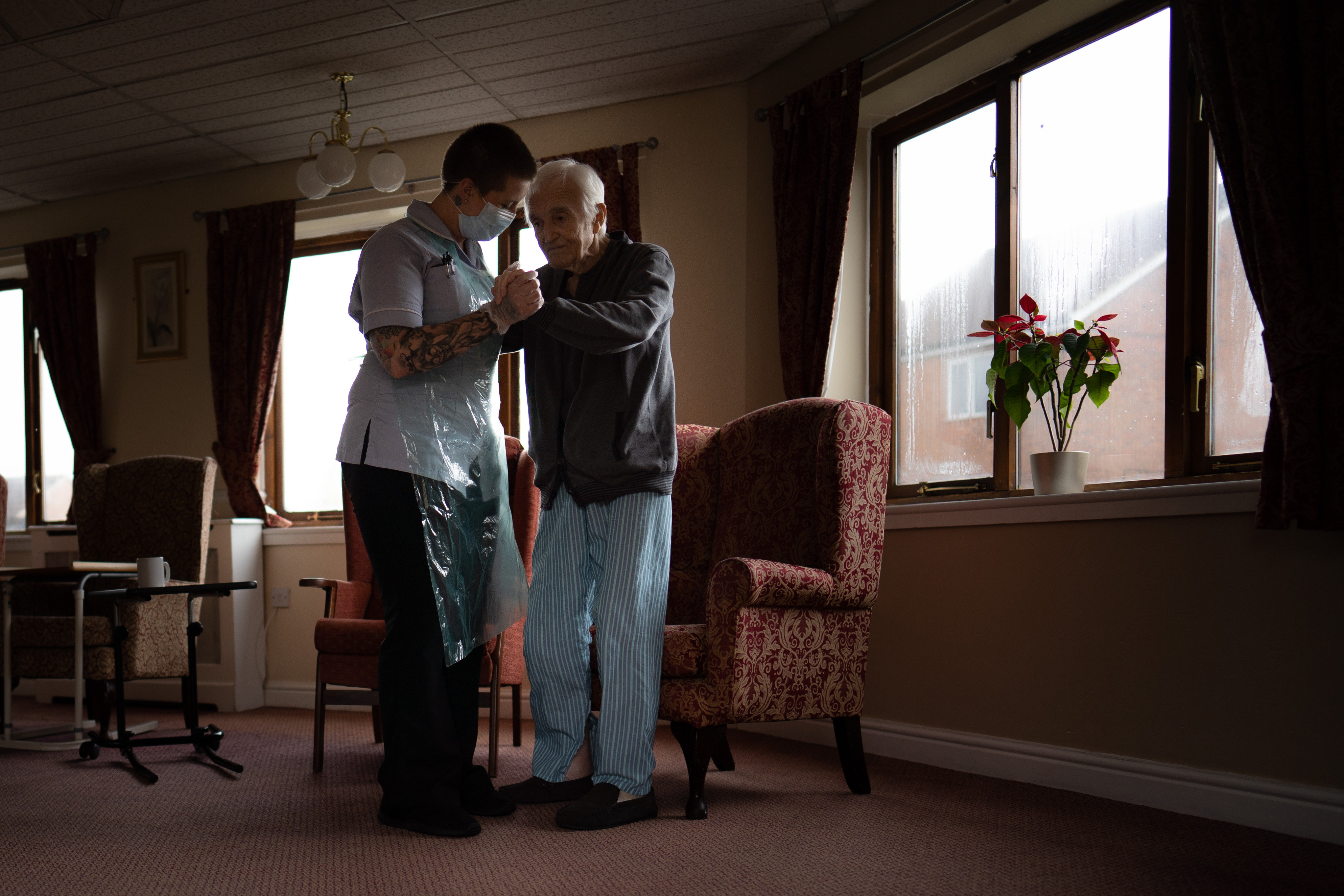 Jack Dodsley, 79, with a carer in PPE at Newfield Nursing Home, Sheffield