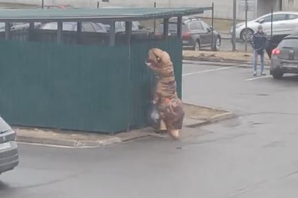 Man takes out the trash in t-rex costume