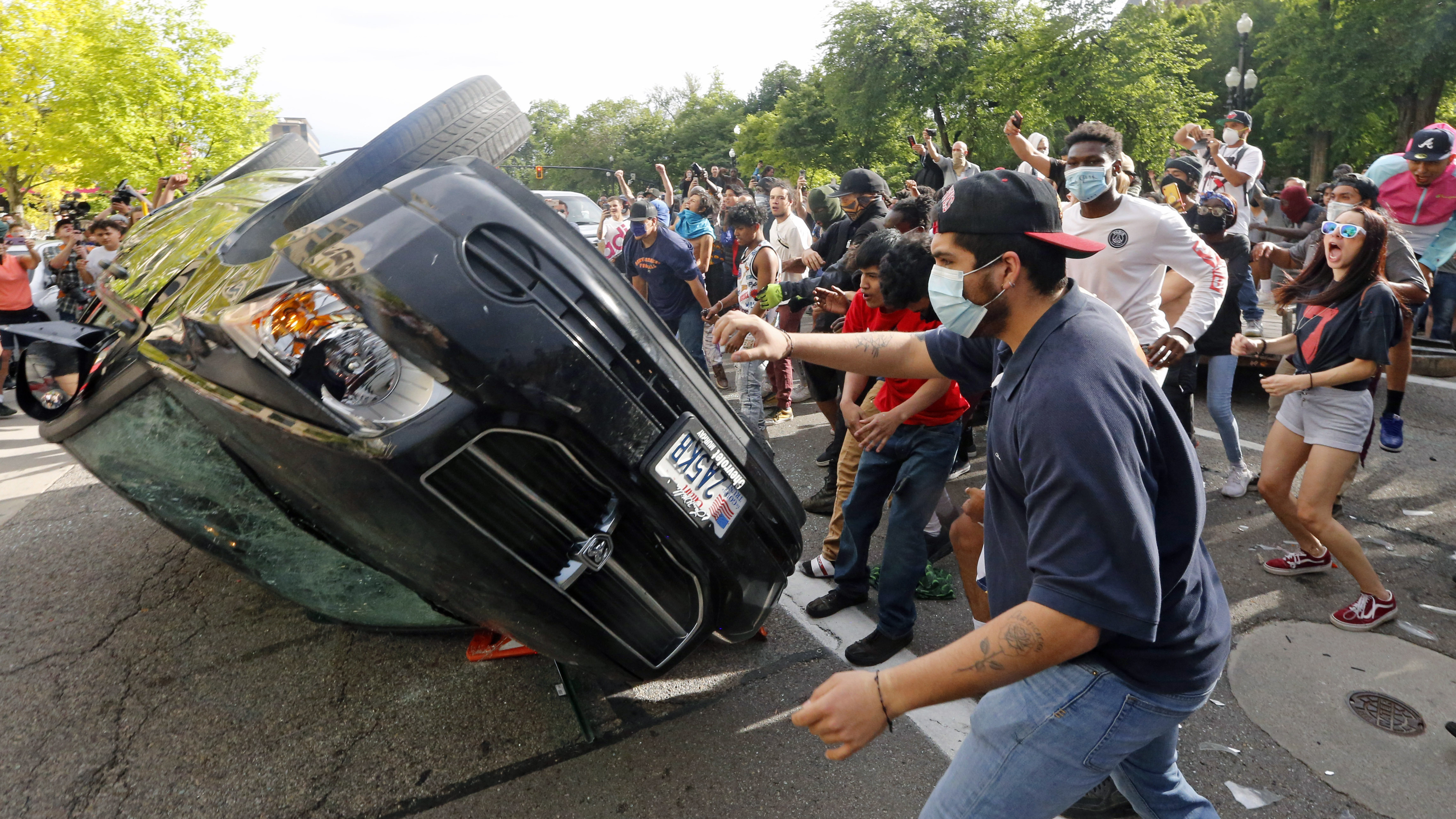 Protestors flip car belonging to man who threatened them with bow and arrow
