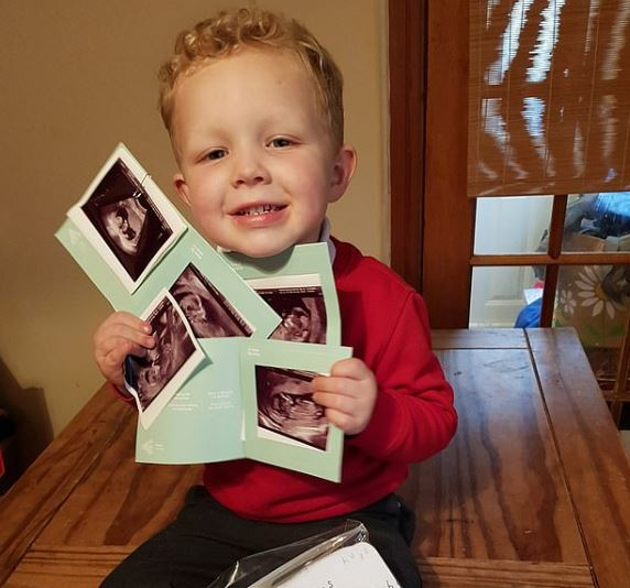 Couple's son holding ultrasound of babies