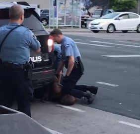 Police officer kneeling on man's neck during arrest