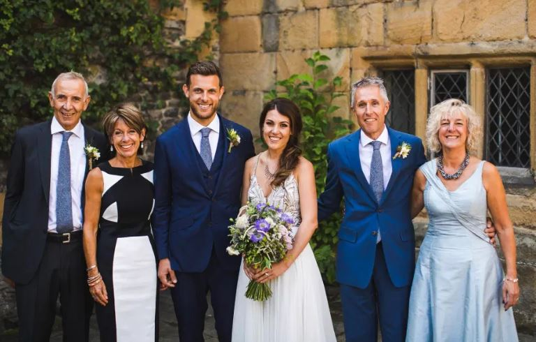 Couple with families on wedding day