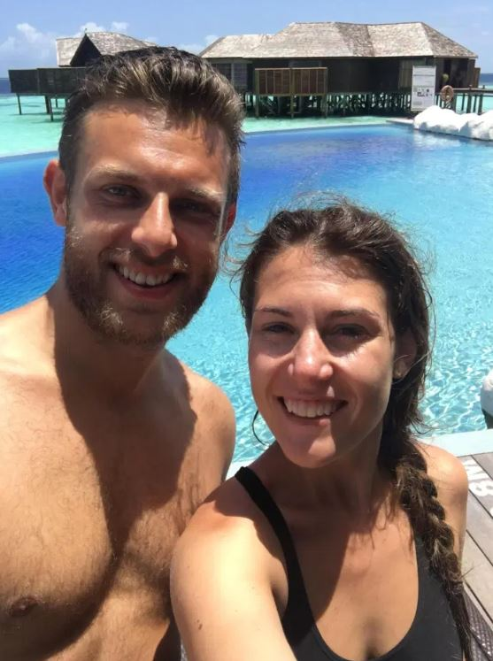 Pair taking selfie on holiday in front of pool