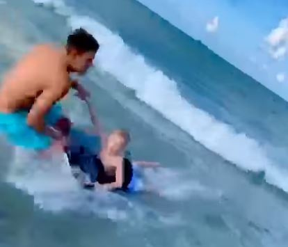 Police officer drags boy away from shark