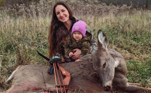 Mum and daughter stood by dead deer
