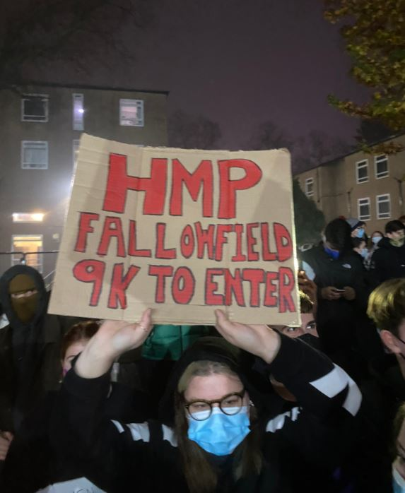 Student holding HMP Fallowfield sign at protest against fences