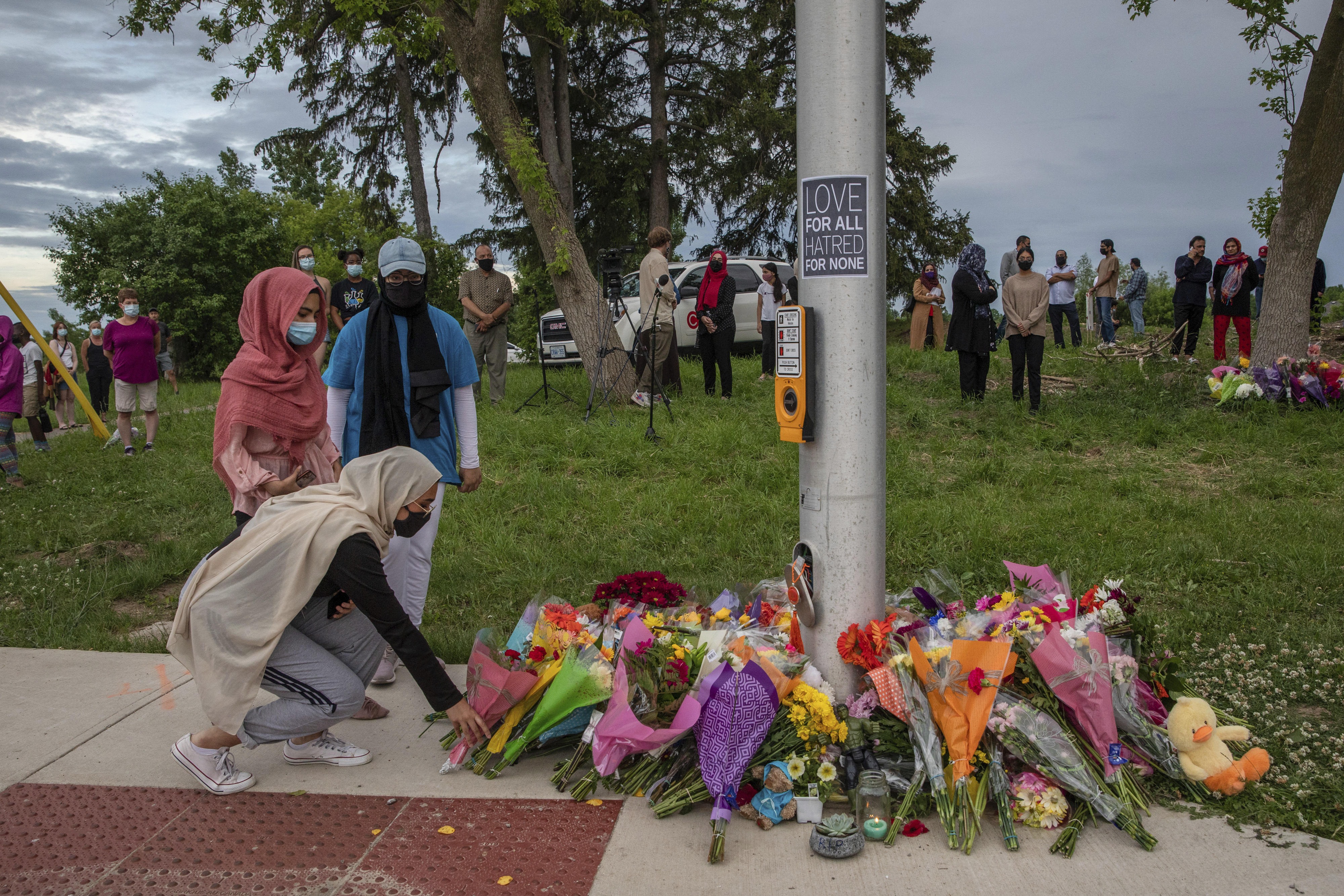 Mourners leave flowers at the site where a family of five was hit by a driver, in London, Ontario (PA)