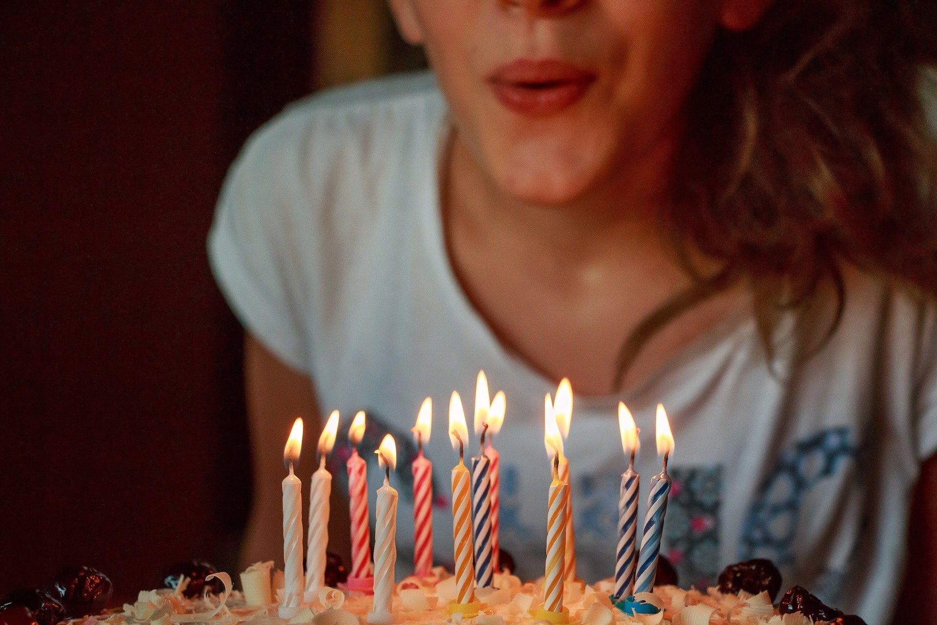 Person blowing out birthday candles (Pixabay)